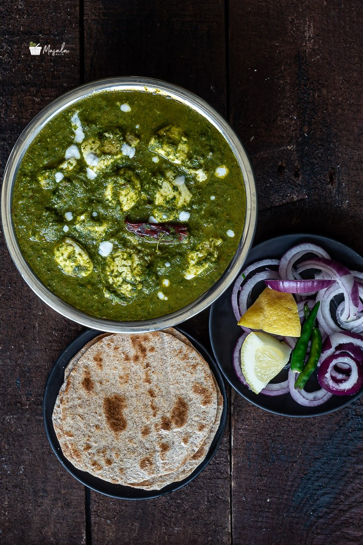 Palak paneer curry served with roti and onions one the side.