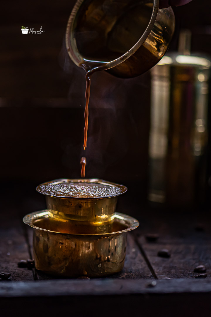 Pouring shot of coffee serverd in a brass dabarah and tumbler