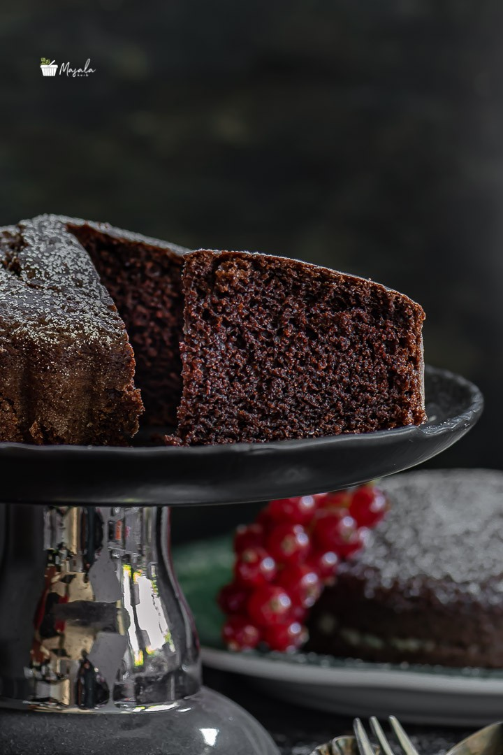 Moist Chocolate Cake slice on a stand served with fruits.
