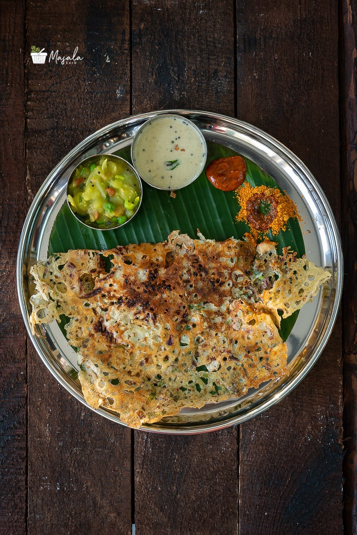 Top angle view of Onion Rava dosa served on a banana leaf with an array of condiments