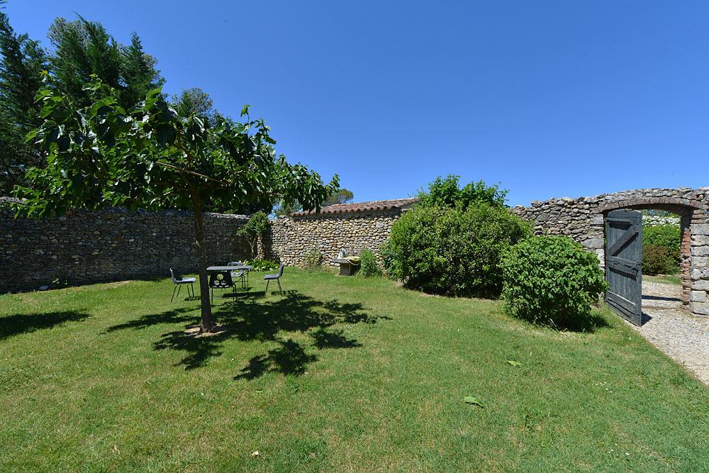 Le jardin ombragé dans le cours intérieur au Mas de la Baillyde, gîtes de charme en Cévennes