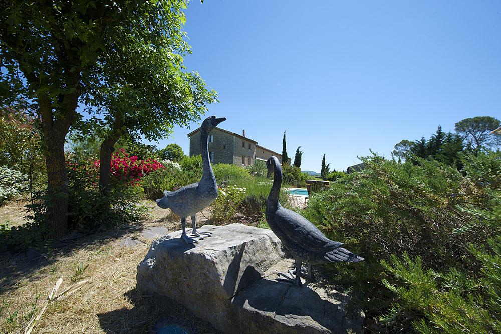 statues des oiseaux au bord de la piscine dans les jardins au Mas de la Baillyde, gîtes de charme en Cévennes
