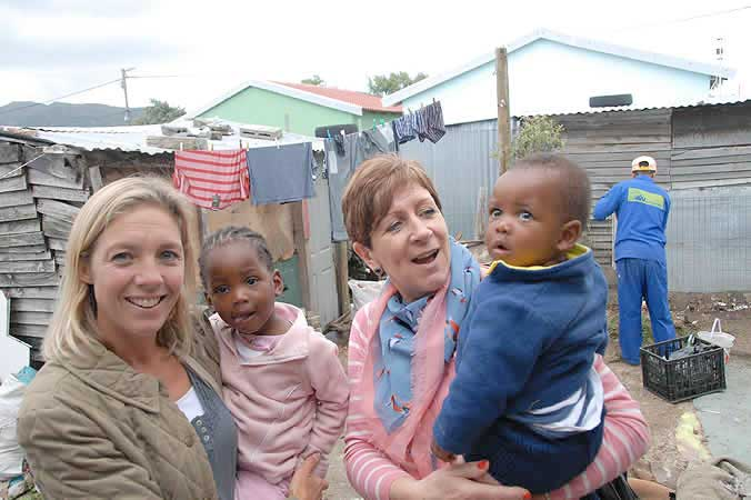 Masicorp's Dr Sophie Billington (left) and Diane Brice of the FACE fundraising team with chidren in the backyard of a soon-to-be refurbished pre-school daycare centre
