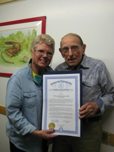 President Diane Watts with Nels Riisberg, a charter member, hold the official state tribute.