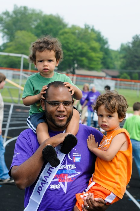 Survivor Justin Ray walks the victory lap with his sons, Walter and Robert in 2013.