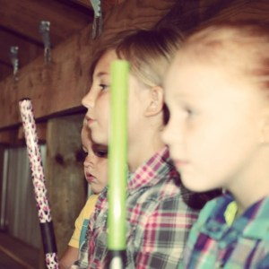 Mikaylah McVicker and Payton Haynes watch and wait their turn at the pig showing. Photo by Myrtie Haynes.