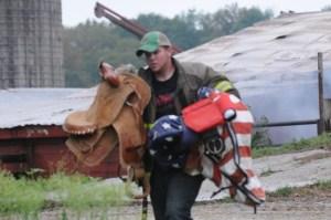 Erik Shafer removes saddles from the barn
