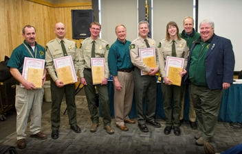 Pictured on the right: Michigan DNR Director Keith Creagh (fourth from left), DNR Parks and Recreation Division Chief Ron Olson (second from right) and Natural Resources Commission Chair J.R. Richardson (far right) honored five PRD employees for their exemplary service when aiding in the rescue of two lost snowmobilers in the Upper Peninsula's Porcupine Mountains. Shown here (left to right) are Bill Doan, Jimmy Newkirk, Justin Farley, Creagh, David Merk, Emily Pleiness, Olson and Richardson.Awardees are holding both DNR Director's Awards and special recognition plaques from the office of Gov. Rick Snyder.