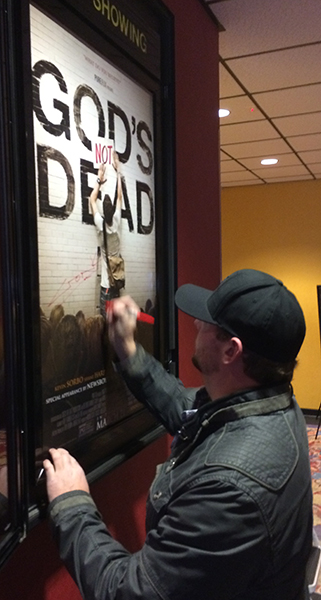 """Cronk signs the cinema's movie poster for """"God's Not Dead."""""""