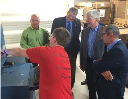 Gov. Snyder, second from right, along with Jim Scatena, CEO of Floracraft; Sen. Hansen and Vic Burwell, vice president of FloraCraft, watch a demonstration.