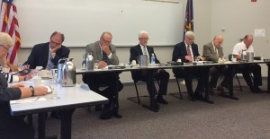 Charles Dillon, in center, listens to the board of trustees meeting.