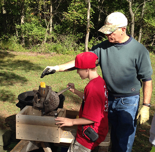 Onekema student, Hunter Harthun works with volunteer Rod Guinan to shell on ear of corn with an antique hand corn sheller.