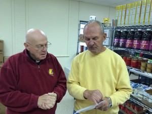 Father Dan DePew, left, talks to volunteer Bill Rosenow.