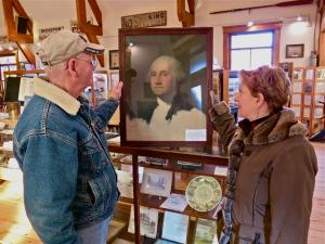 Museum Director Ed Bigelow and Amy LaBarge look at one of the museum's most recent acquisitions -- the print of Gilbert Stuart's famous 1796 unfinished oil painting of George Washington that for many years hung in the old Pentwater School top-floor assembly room. Local resident Bill Lovell purchased it for $1.50 just prior to the school's demolition in 1967.