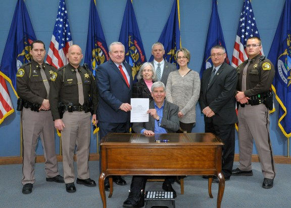 State Rep. Ray Franz, R-Onekama, and Gov. Rick Snyder display Public Act 441, a new law naming a portion of M-116 in Mason County after fallen State Police Trooper Paul Butterfield. Also (from left): Chief Deputy Steve Hansen, Deputy Jeremy King, Pat Butterfield, Rep. Jon Bumstead, Jennifer Sielski, Sheriff Kim Cole and Deputy Brandon Romero.