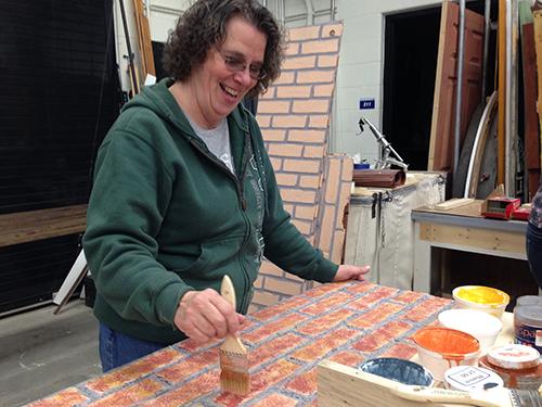 Marty Cupp paints the set.