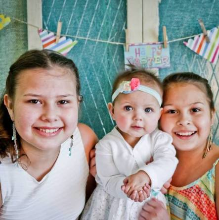 Kaya, 12 and Ana, 10 holding Lauren, now 10- months-old.