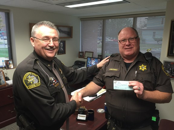 Jim Lindenau, president of the Clown Band, right (also a MCSO deputy) hands a check to Sheriff Cole.