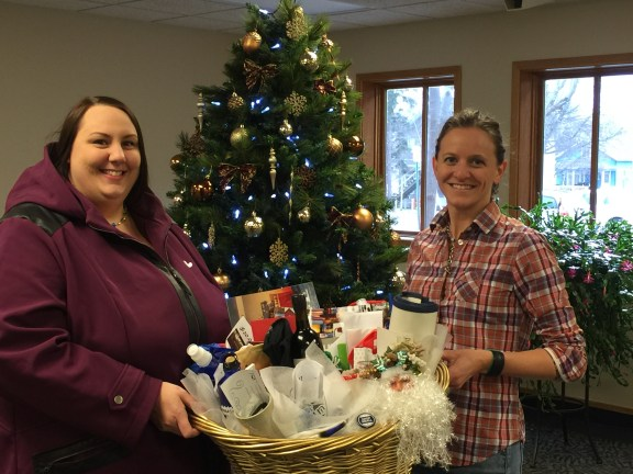 Rachel Collings, left, excepts the gift basket from Jen Tooman.