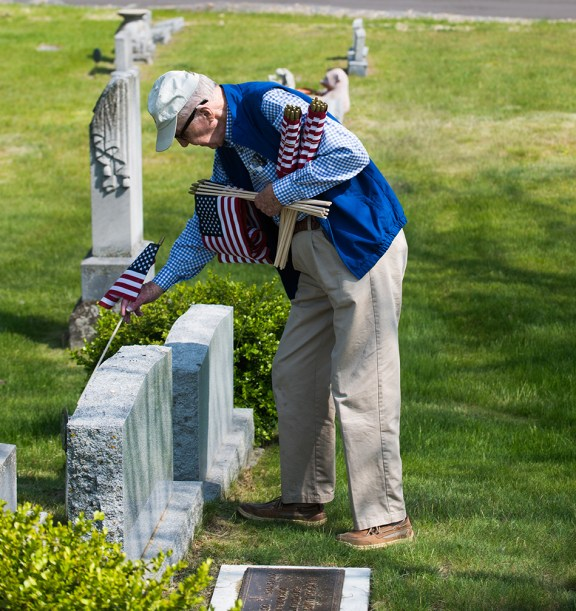 Jack Rasmussen places a flag on a veteran's grave.