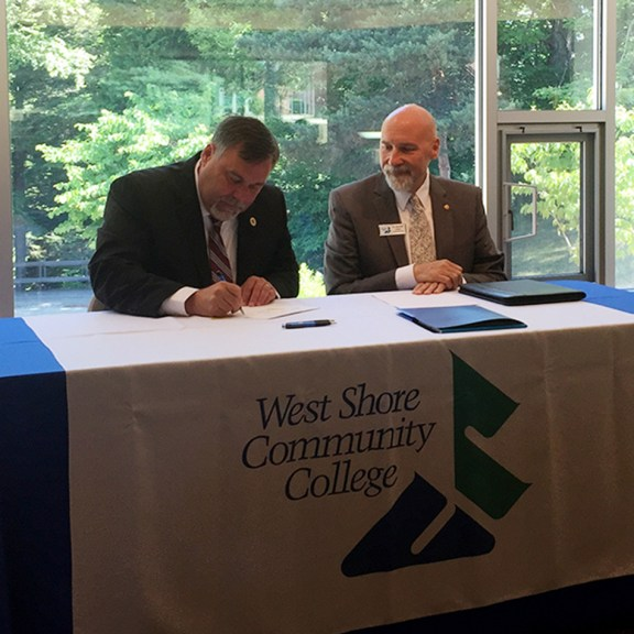 Dr. Randy Showerman, left, of MSU signs the agreement as WSCC President Kenneth Urban watches.