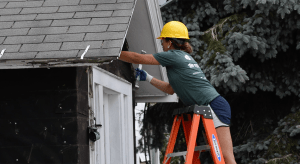 Volunteers take off siding on a house at 201 N. William St. in Ludington.