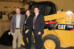 Seth, right, and Lyndsay Earl with a representative from Michigan Cat during the state annual meeting.