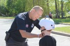 Easthampton School Resource Officer Alan Schadel helps a child with his new bicycle helmet.