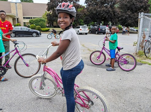 Young child receives a free bike from The Bike Connector in Lowell and a free Project KidSafe bike helmet from Breakstone, White & Gluck, a Boston law firm.