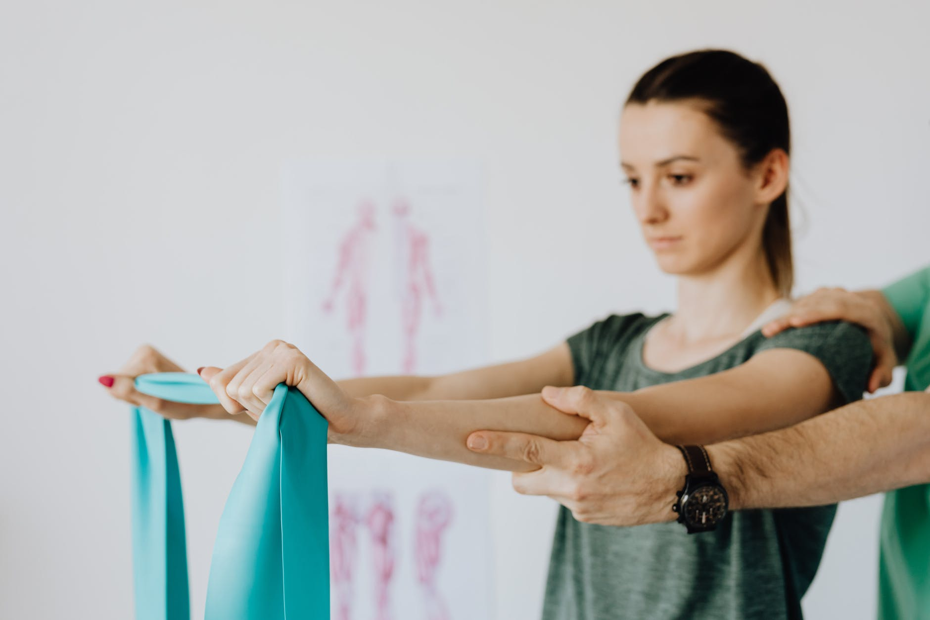 woman stretching elastic tape during medical examination by crop orthopedist