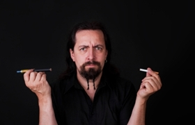 handsome caucasion man holding electronic and ordinary cigarette