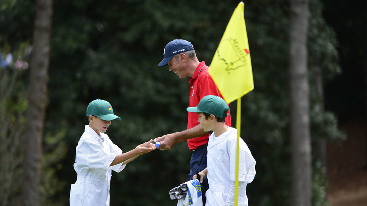 Matt Kuchar presents a putter to his son, Carson, on the first hole during the 2018 Par 3 Contest while his other son, Cameron, looks on.