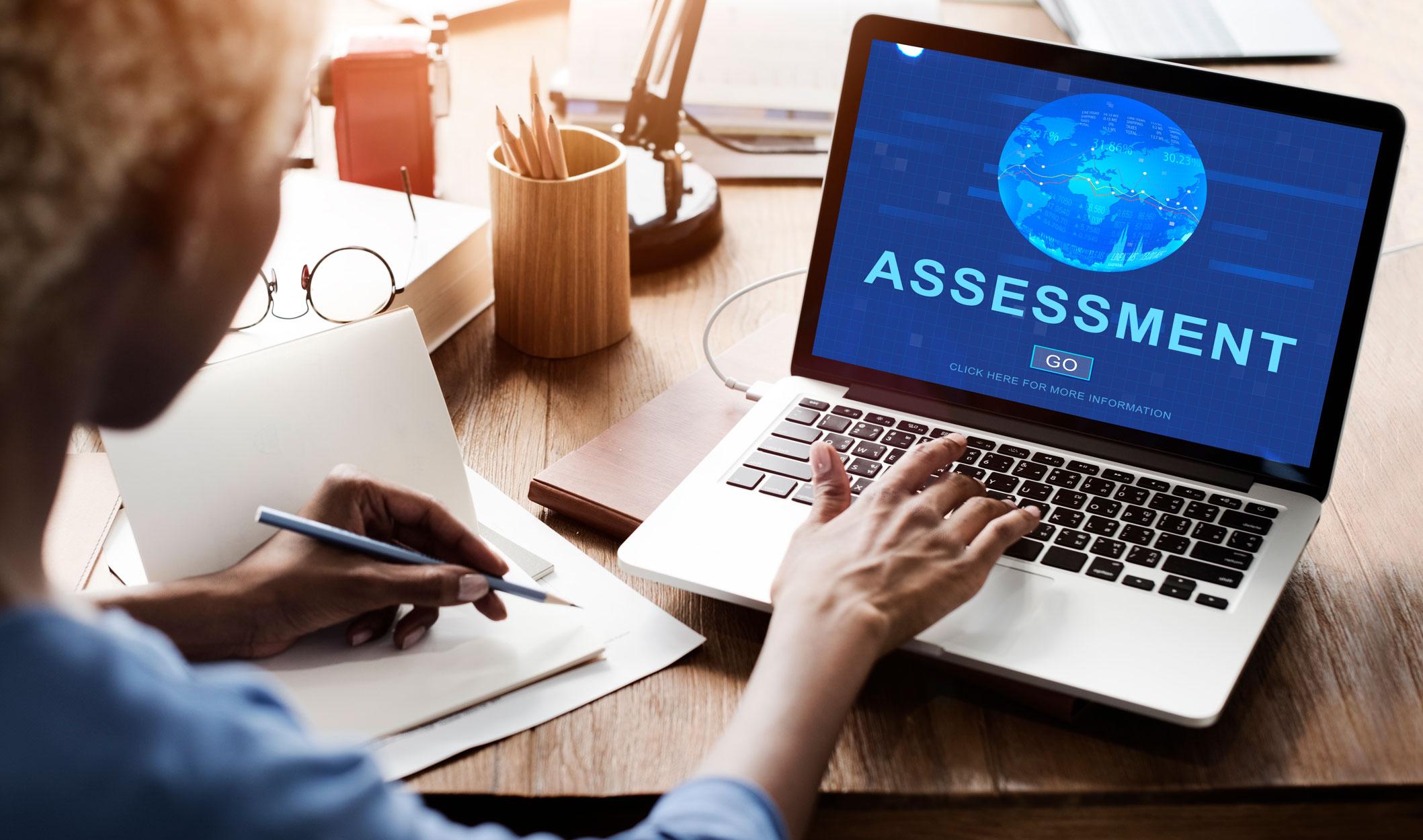 e-Learning-development-multilingual-DTP-multilingual-desktop-publishing-assessment-laptop-world-woman-typing-holding-pencil-papers-desk