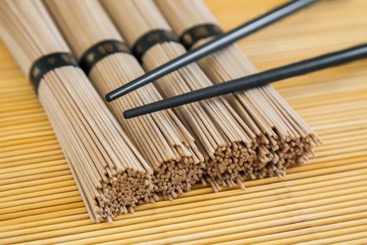 close-up bundles of soba noodles and black chopsticks on bamboo background