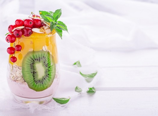 Smoothies for breakfast layers of mango and berries with a layer of oatmeal is decorated with a slice of kiwi in the center and sprigs of red currants and mint. Concept of healthy food. selective Focus