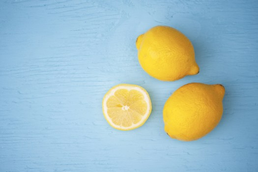 Macro view of vibrant yellow lemon slice and two whole lemons on rustic wooden teal table background shallow DOF