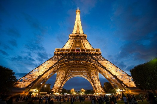 PARIS FRANCE - JULY 27 2015: Tourists are visiting the eiffel tower in the twilight in Paris in France