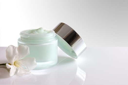Glass open jar with facial or body cream on white table. with lid and flower. White isolated background . Front view.