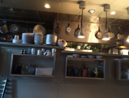 The kitchen along the left wall of the restaurant.
