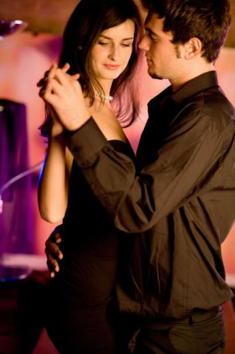 Young couple dancing at the restaurant or cafe