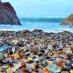 A praia que não tem areia, mas cacos rolados de vidro colorido