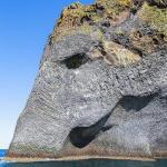 Elefante de pedra bebe água com tromba mergulhada no mar