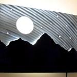 Céu com lua e estrelas atrás das montanhas em painel iluminado