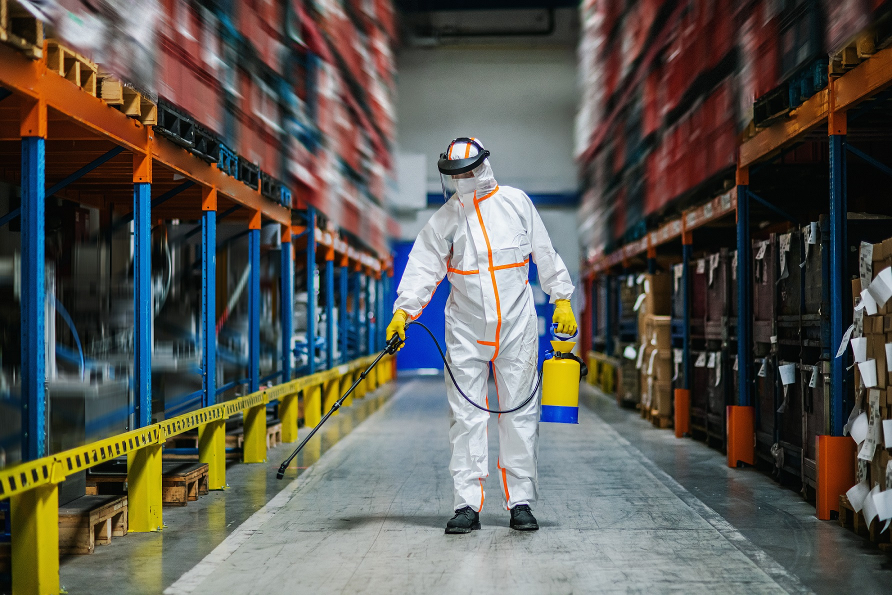 Man wearing protective mask and cloth disinfecting warehouse