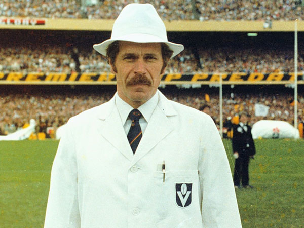 A VFL goal umpire in white coat and hat