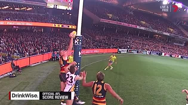An AFL defender who may or may not be touching the ball as it crosses the line.