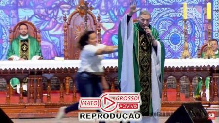 Sem qualquer razão aparente a mulher surge do nada e se empurra com toda força o Padre de cima de um palco de 2 metros.