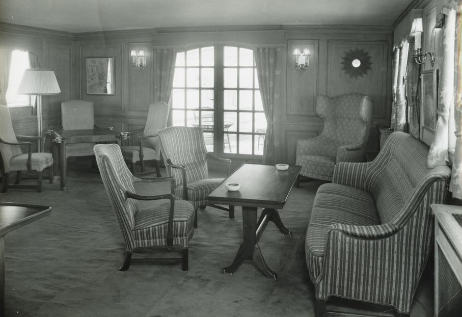 Røkesalongen på øverste dekk på Kongeskipet Norge med møbler tegnet av Rastad & Relling. Bord produsert av A. Huseby & Co. og stoler og sofaer utført av Arnestad Bruk.