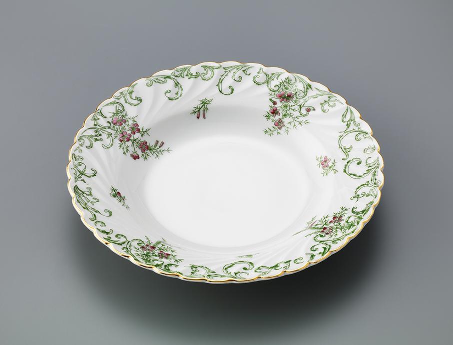 Dyp tallerken i porselen med trykket dekor på sidene.