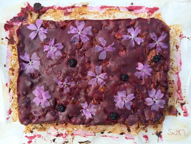 Home-baked apple and blackberry cake with elderberry icing and marrow flowers
